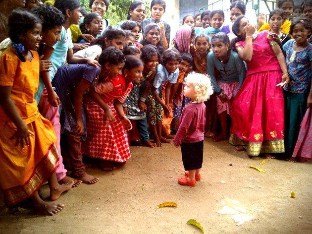 Criança branca observada por indianas